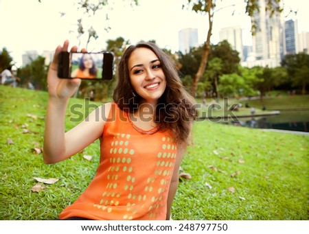 girl sitting in the park of Kuala Lumpur on the background of business centers and makes selfie, happy - stock photo