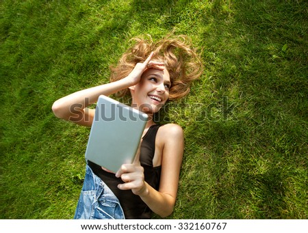 girl sitting in the park  on the background of grass, happy