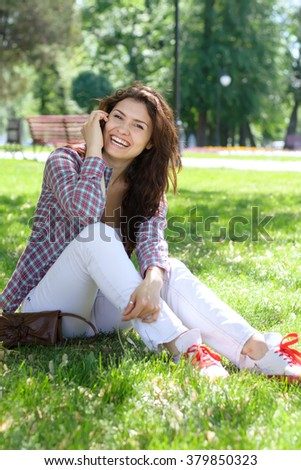 Girl sitting in the park on the grass and talking on the phone and laughing. Concept: study, college, exam, knowledge, communication