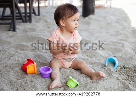Girl sitting in the sand  playing and laughing - stock photo