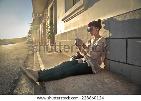 Girl sitting in the sun and using her phone  - stock photo