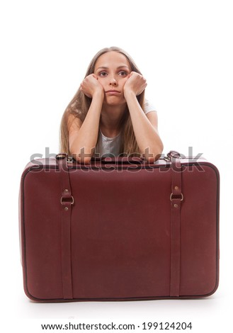 girl sitting near a suitcase, isolated on white background