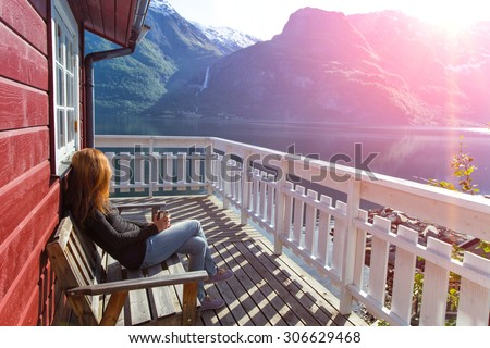 girl sitting near rorbu and admires the beautiful Norwegian landscape at the fjord and mountains - stock photo
