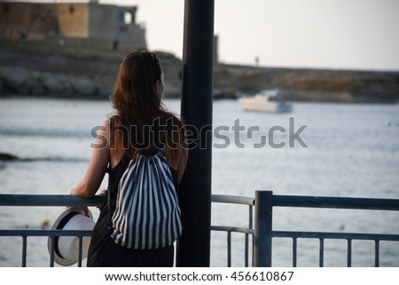 girl sitting next to a street light on an island near the sea