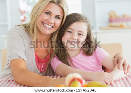 Girl sitting next to her mum at the kitchen embracing with fruit on the table - stock photo