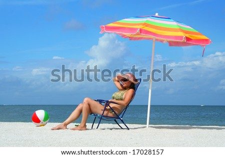 Girl sitting on a beach chair under an umbrella enjoying a sunny day at the beach. - stock photo