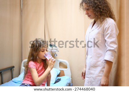 Girl sitting on a bed and drinking water near medical worker in a hospital ward - stock photo