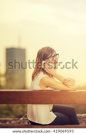 Girl sitting on a bench and talking on the phone with city background.
