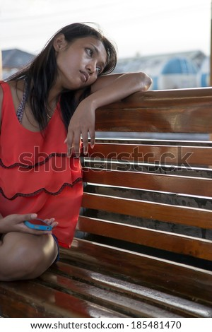 girl sitting on a bench at the train station