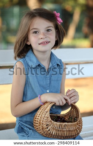 Girl sitting on a bench with a wicker basket. - stock photo