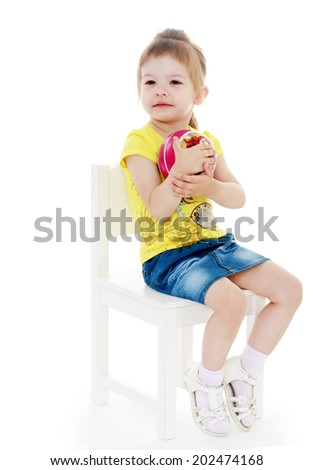 girl sitting on a chair and hugs ball looking to the side.passionate child for interesting occupation,active lifestyle,happiness concept,carefree childhood concept. - stock photo