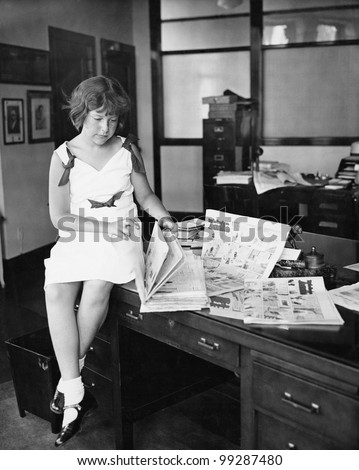 Girl sitting on a desk and reading a newspaper - stock photo