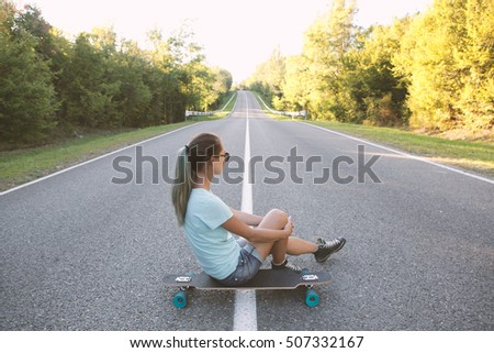 Girl sitting on a longboard and staring at the road. Toned image.