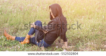 girl  sitting on a meadow grass and enjoying a sunset