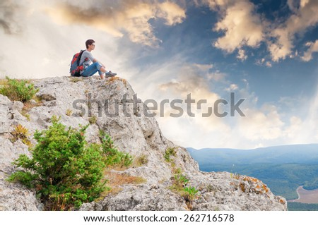 Girl sitting on a mountain and looking on the valley - stock photo