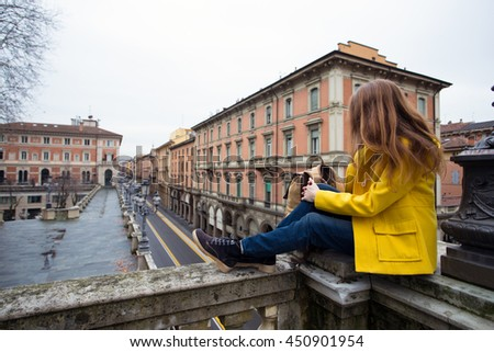 girl sitting on a parapet and looking at the Bologna streets
