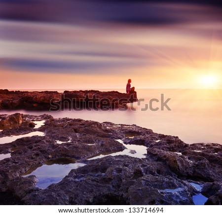 Girl sitting on a rock by the sea and watching the beautiful sunset - stock photo
