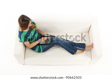 Girl sitting on a sofa using a tablet and navigate on a website. (the website is fake and the image belongs to me)