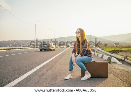 Girl sitting on a suitcase at the roadside. Image with sunlight effect. - stock photo