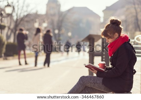 Girl sitting on a wooden bench, reading a book and drinking coffee, outdoors - stock photo