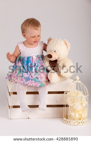 girl sitting on a wooden box with a bear - stock photo