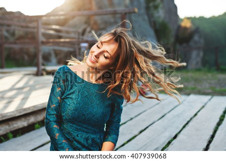 Girl sitting on a wooden path, outdoor. Her head bowed aside, fluttering hair, closed eyes, smiling. Woman wearing blue dress. Waist up. Sunshine - stock photo
