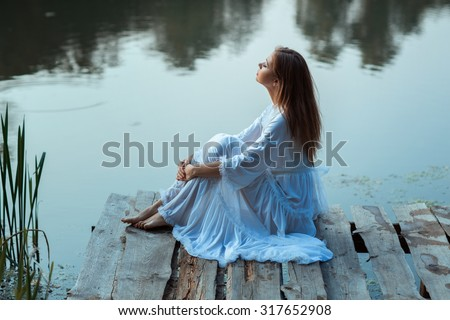 Girl sitting on a wooden pier and dreams. On the morning at sunrise. - stock photo