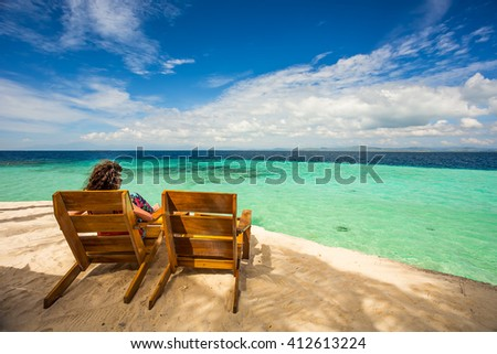 Girl sitting on beach chair and enjoying the view / Beach chairs, clear water and beautiful view on Modessa tropical island, near Palawan, Phillippines - stock photo