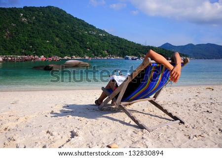 Girl sitting on beach chairs on tropical white sand beach in koh tao, thailand - stock photo