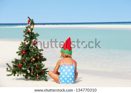 Girl Sitting On Beach With Christmas Tree And Hat - stock photo
