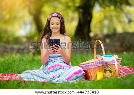 Girl sitting on blanket and using tablet in the park