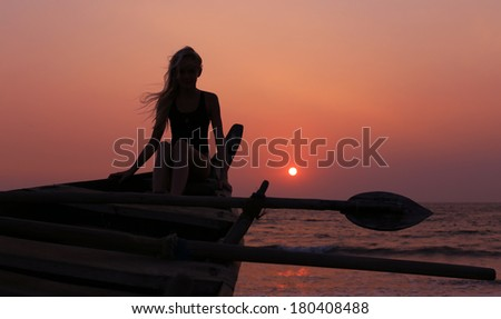 girl sitting on boat at sunset background