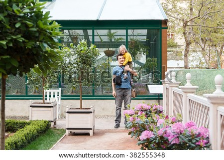 girl sitting on Daddy shoulders in the garden - stock photo