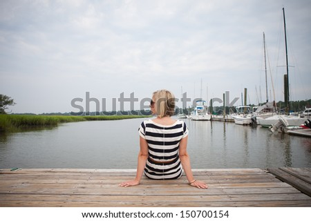 Girl sitting on dock looking to the side. - stock photo