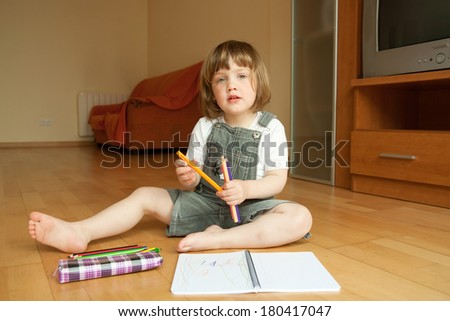 girl sitting on  floor and drawing.