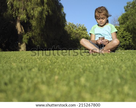 Girl (6-8) sitting on grass in park, listening to MP3 player, front view, surface level - stock photo