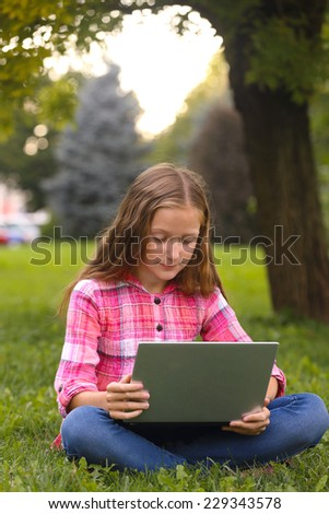 girl sitting on grass with notebook