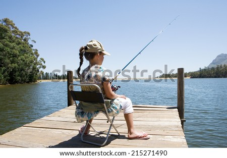 Girl sitting on jetty, fishing in lake, rear view - stock photo