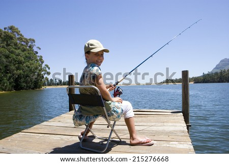 Girl sitting on jetty, fishing in lake, smiling, rear view, portrait - stock photo