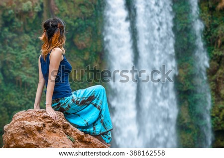 Girl sitting on rock and looking at waterfall background. Ouzoud falls in Morocco. - stock photo