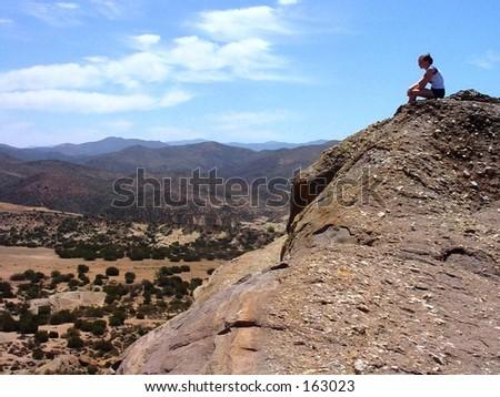 Girl sitting on rock at Vasquez Rocks, California - stock photo