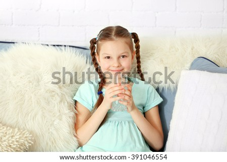 Girl sitting on sofa and drinking water indoors - stock photo