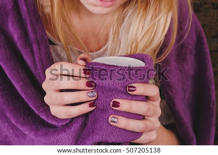Girl sitting on sofa in livingroom with cup of tea