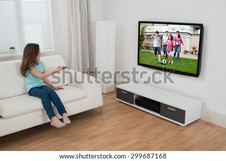 Girl Sitting On Sofa Watching Television In House - stock photo