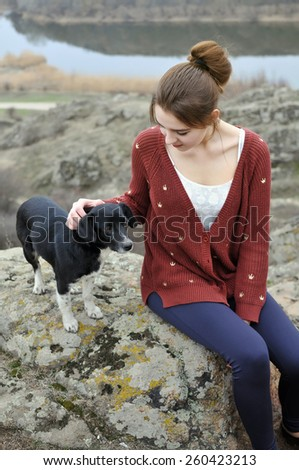 Girl sitting on stone with dog