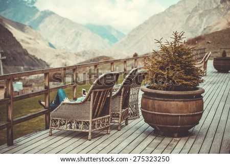 Girl sitting on terrace with beautiful mountain view. Toned image - stock photo