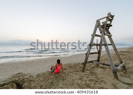 Girl sitting on the beach after running at dawn near the lifeguard chair - stock photo