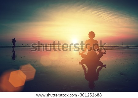 Girl sitting on the beach during sunset and meditating in yoga pose. Runner girl in the background. - stock photo