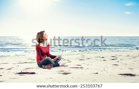 Girl sitting on the beach with a computer