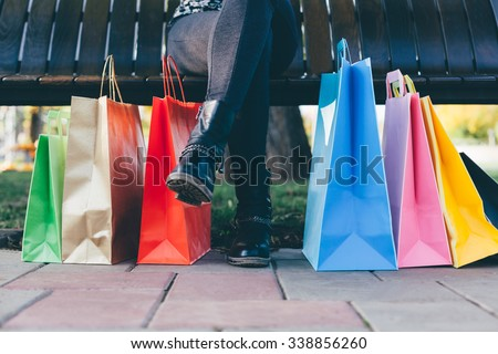 Girl sitting on the bench with colorful shopping bags - stock photo